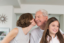 Adult daughter kissing father with granddaughter at their side