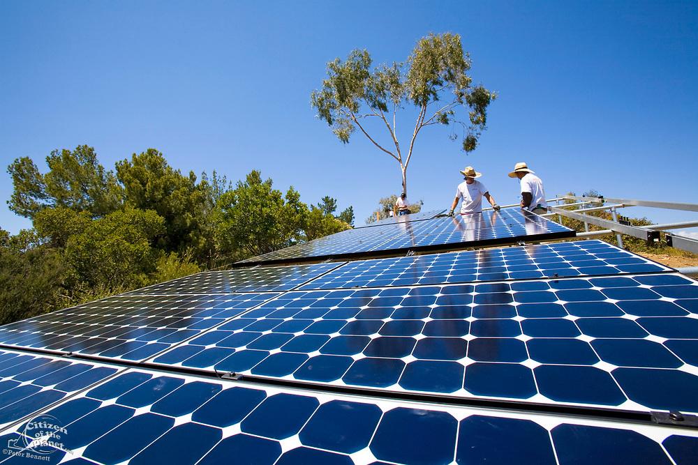 Workers install a solar array on a hillside in Malibu, Installation by Martifer Solar USA, California, USA