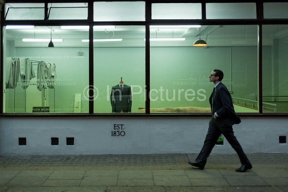 A man walks past the window of London Fashion Workrooms, a  on 4th December 2017, in London England. Established in 1892 as a formalwear manufacturer, The London Fashion Workrooms branched into alterations in the 1970s. The first large fashion workroom was launched in 1997 specifically to service the shops and boutiques of London's west end. Based in Covent Garden with a 4000 square foot purpose built unit, we presently provide garment alteration services to 38 high-end London stores and many private clients. With 20 tailors on site we have the skills and personnel necessary to provide a one-stop service.