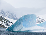 Blue iceberg shapes jut from the Southern Ocean offshore from Graham Land, the north part of the Antarctic Peninsula, Antarctica.