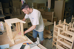 Cabinet maker constructing carcass of bedside cabinet,