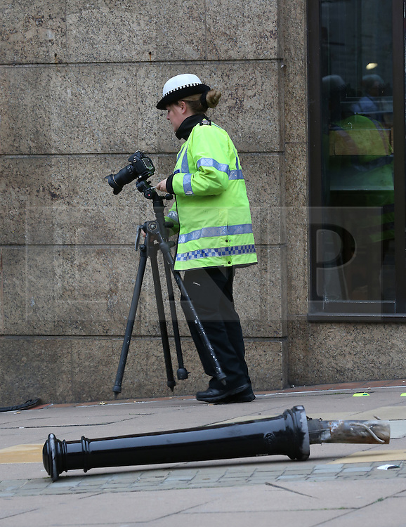 © Licensed to London News Pictures. 23/10/2015. Guilford, UK. . A police officer gathers evidence at the entrance to The Friary shopping centre after a car injured a number of pedestrians. The displaced bollard is believed to have been hit by the car. Photo credit: Peter Macdiarmid/LNP