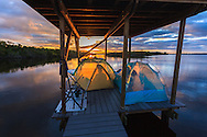 Sunrise greets boat campers who have spent the night in their tents on a chickee platform on the Wilderness Waterway in Everglades National Park, Florida.<br /> WATERMARKS WILL NOT APPEAR ON PRINTS OR LICENSED IMAGES.<br /> <br /> Licensing: https://tandemstock.com/assets/99802570