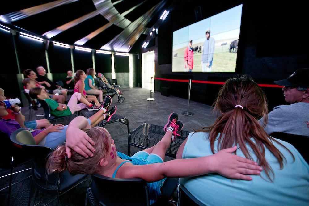 "Fairgoers watch a video on Nebraska agriculture in the grain bin theaer at the ""Raising Nebraska"" exhibit Saturday in the Nebraska Building at the Nebraska State Fair in Grand Island. (Independent/Matt Dixon)"