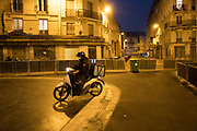 """March, 17th, 2020 - Paris, Ile-de-France, France: Deliveroo service motorbike rider wearing mask. Food delivery services continue, even though restaurants are closed, during the first day of near total lockdown imposed in France, to combat the Coronavirus. President of France, Emmanuel Macron, said the citizens must stay at home from midday on Tuesday for at least 15 days. He said """"We are at war, a public health war, certainly but we are at war, against an invisible and elusive enemy"""". All journeys outside the home unless justified for essential professional or health reasons are outlawed. Anyone flouting the new regulations would be punished. Nigel Dickinson"""