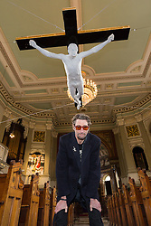 "© Licensed to London News Pictures. 19/02/2015. London, UK. Artist, Nick Reynolds with his lifesize marble crucifixion sculpture of Pete Doherty, called ""For Pete's Sake"", which is unveiled at St. Marylebone Parish Church in London and seen suspended above the aisle of the 200-year-old church. The life-size sculpture was made in 2008 as a collaboration between Pete Doherty and artist, Nick Reynolds. This is the first time the sculpture has been publically displayed and it is part of the exhibition in aid of a fund to help find Tom Moore, who went missing in 2003 called Stations of the Cross, which runs until 17th March and shows other works that make reference to the Passion of Christ. Photo credit : Vickie Flores/LNP"