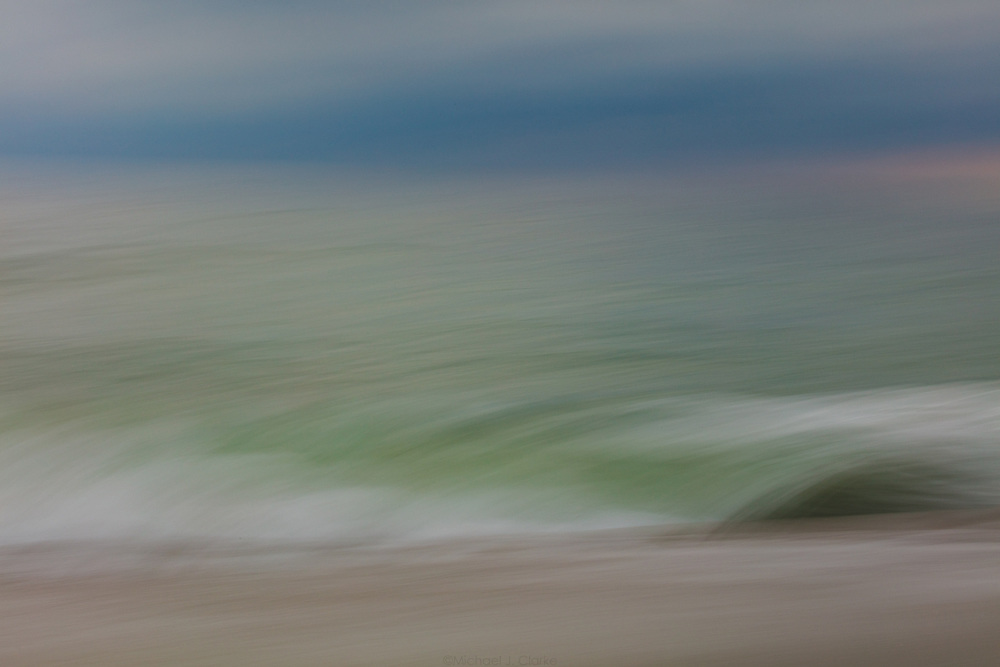 Atlantic Ocean waves curling in the sandy shores of Miacomet Beach on an autumn evening.