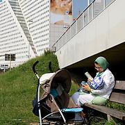 Nederland Rotterdam 7 juni 2007 20070607.Moslim vrouw voedt baby met de fles op een bankje aan de maasboulevard, op de achtergrond een reusachtig grote reclame op billboard gebouw Ernst & Young aan de Boompjes met halfnaakte man van Dolce Gabbana.Reclametechnieken: Bekend is de formule AIDA: attention, interest, desire, action: de aandacht opwekken, de interesse wekken, het verlangen opwekken, tot actie overhalen.Mental Preference: Techniek om mensen op een of meerdere van hun mentale denkstijlen aan te spreken: logisch; pragmatisch; emotioneel of creatief.Associatie: Reclamemakers proberen hun product te associÇren met aangename of begeerlijke dingen om hun eigen product even begerig te maken. Hiervoor gebruiken ze modellen, landschappen en ander vergelijkbaar beeldmateriaal.Aspirationele leeftijd: Door de boodschap te richten op de aspirationele leeftijd van de doelgroep, wordt deze voor de daadwerkelijke doelgroep aantrekkelijker..Foto David Rozing
