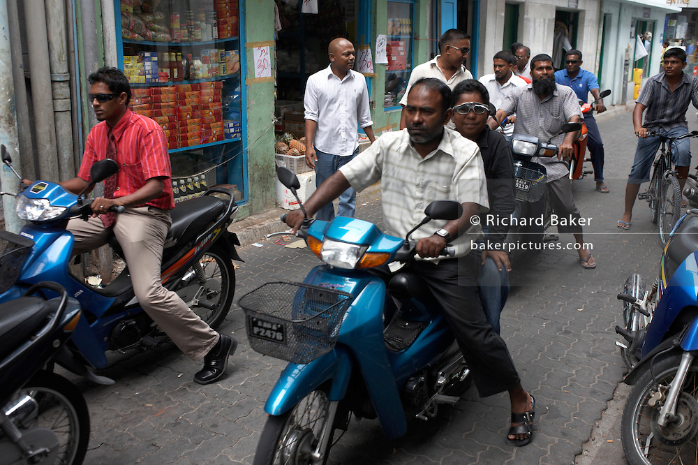 Motorcycles, mopeds and their helmetless riders crowd a narrow urban street of Male, the capital of Maldives