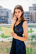 Young woman in formal dress takes notes on a yellow legal pad while talking on a mobile phone on the balcony of her home