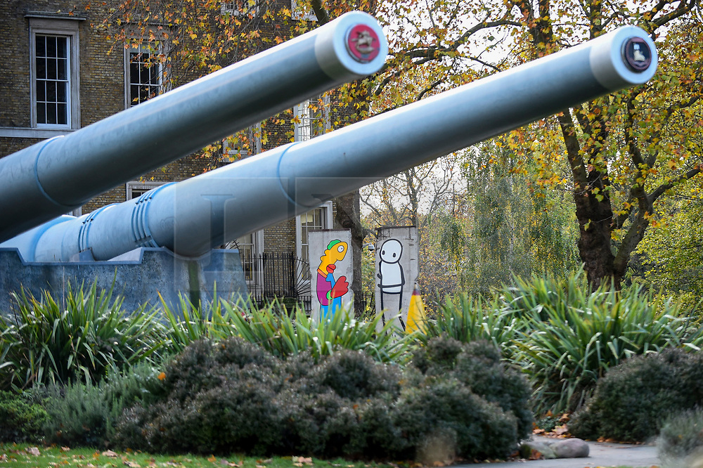 © Licensed to London News Pictures. 05/11/2019. LONDON, UK.  Unveiling of new work by artists Theirry Noir (L) and STIK (R) on original Berlin Wall sections to mark 30 years since the fall of the Berlin Wall, seen against the big guns outside the Imperial War Museum.  The new works reflect the symbolic connections between the Berlin Wall and street art and the fall of the wall on 9 November 1989.  These new works are on display until 1 December.  Photo credit: Stephen Chung/LNP