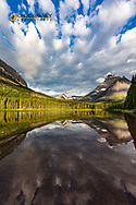 Mountains reflect into Fishercap Lake in Glacier National Park, Montana, USA
