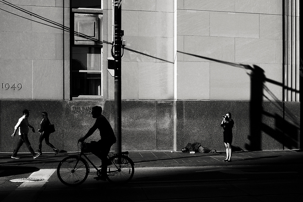This photograph is all about shadow and light. I was attracted to the girl taking a photograph and the street person lying behind her. The shadows from the lampposts really strengthened the composition and the passing bike was fortuitous and resulted in a really clear silhouette. The frame also has more interest because of the two people walking. This image is definitely one my favourite. It was photographed near King and Bay Streets