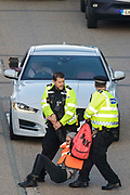 Surrey Police officers drag an Insulate Britain climate activist from the anticlockwise carriageway of the M25 between Junctions 9 and 10 on 21st September 2021 in Ockham, United Kingdom. Activists briefly blocked both carriageways of the motorway as part of a campaign intended to push the UK government to make significant legislative change to start lowering emissions before they were removed and arrested by Surrey Police.
