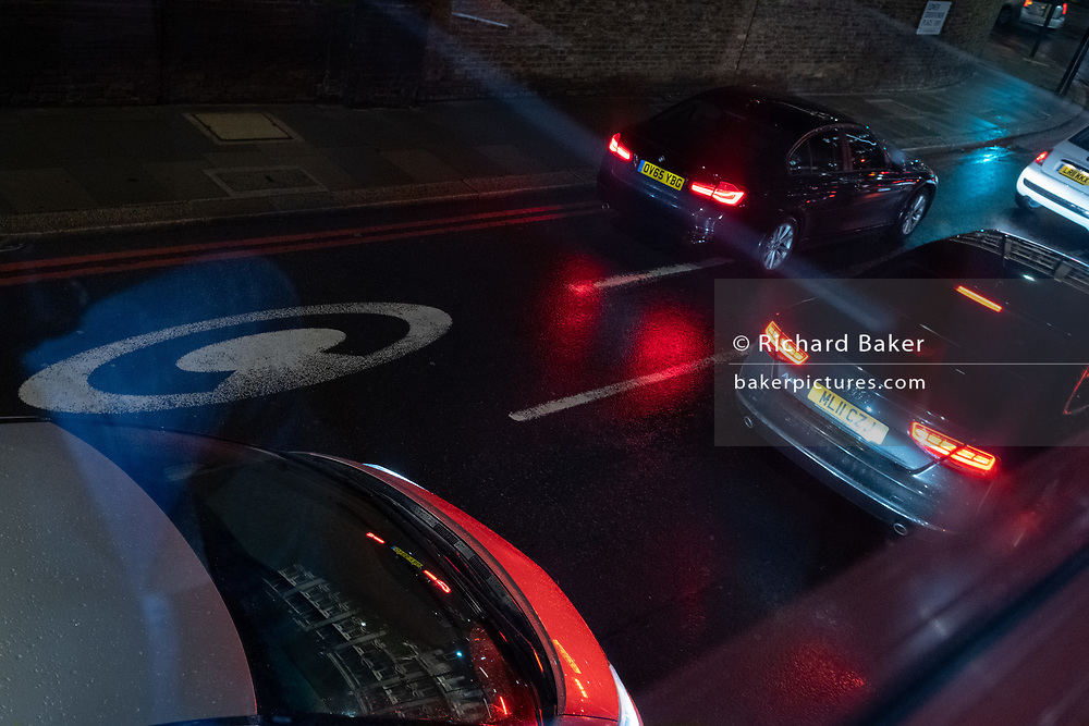 Seen from a London bus on a rainy night in the West End, cars queue in traffic at the edge of the Congestion Charge zone whose times of operation have temporarily changed to seven days a week during the Coronavirus pandemic, on 27th August 2020, in London, England.