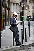 A man reads a newspaper on the Rue Mouffetard.<br /> Rue Mouffetard is in the Fifth (cinquieme) arrondisement and the street is very old: originally a Roman rod running from the Roman Rive Gauche city south the Italy. The market is famous for it's quality fresh produce and artisanal food shops.
