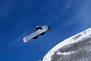 Male snowboarder flying through the air.