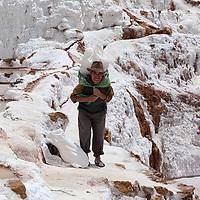 A man carrying a big bag of salt under the midday sun.