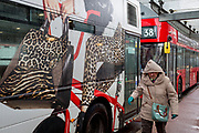 An elderly lady passenger walks through autumnal rain, next to a London bus that features an ad of style and fashion, while stopped at Victoria Station, on 17th October 2019, in London, England.