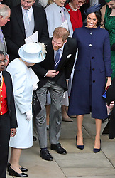 File photo dated 12/10/18 of Queen Elizabeth II speaking with the Duke and Duchess of Sussex outside St George's Chapel in Windsor Castle, following the wedding of Princess Eugenie to Jack Brooksbank. The Duke and Duchess of Sussex are expecting a baby in spring 2019, Kensington Palace has announced.