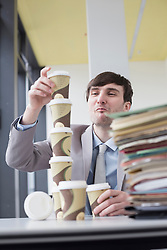 Businessman building tower with coffee cups, smiling