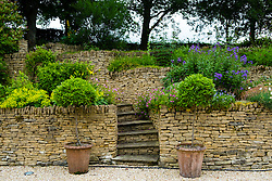 View of country terraced domestic garden made from walls of Cotswold stone in England, United Kingdom