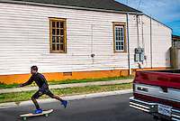 NEW ORLEANS - CIRCA FEBRUARY 2014: Young man skate boarding in the streets of McDonough, a popular community within the city of New Orleans in Louisiana.