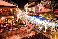 High angle nighttime view of crowds of tourists walking on West Street in Yangshuo, China.