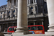 Pillars of Royal Exchange and the Bank of England with a passing London bus and sunbathing woman.
