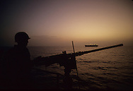 Guard duty on the USS Foxx.  Photograph made as part of a DOD pool that went to the Fox to cover the reflagging of oil tankers in Persian Gulf in July 1987,  The tanker is in the background...Photograph by Dennis Brack bb24