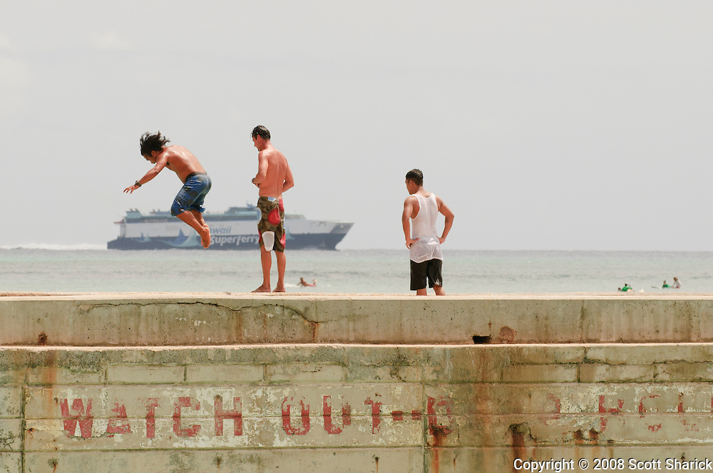 A boy jumps off a pier in front of the Hawaii Super Ferry in this picture from Hawaii.