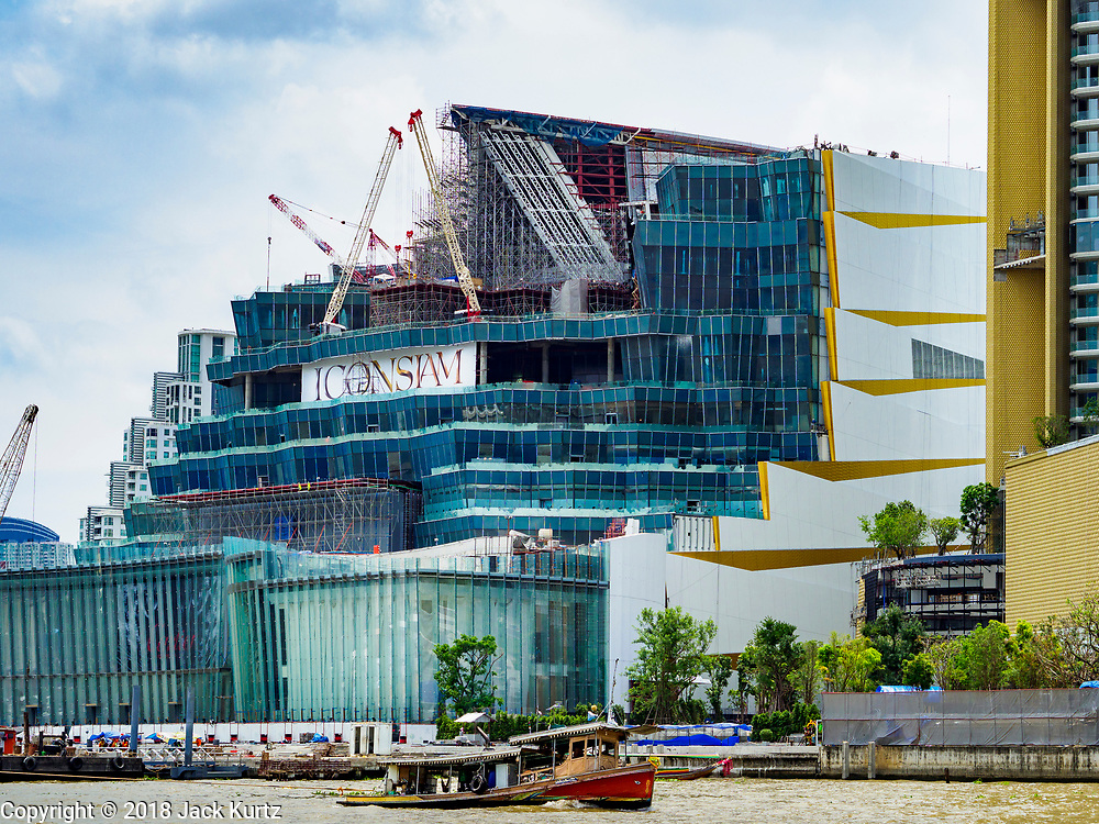 17 SEPTEMBER 2018 - BANGKOK, THAILAND:  A tugboat goes up the Chao Phraya River past the ICONSIAM development as seen from the Bangkok side of the river. ICONSIAM is a mixed-use development on the Thonburi side of the Chao Phraya River. It is expected to open in 2018 and will include two large malls, with more than 520,000 square meters of retail space, an amusement park, two residential towers and a riverside park. It is the first large scale high end development on the Thonburi side of the river and will feature the first Apple Store in Thailand and the first Takashimaya department store in Thailand.    PHOTO BY JACK KURTZ