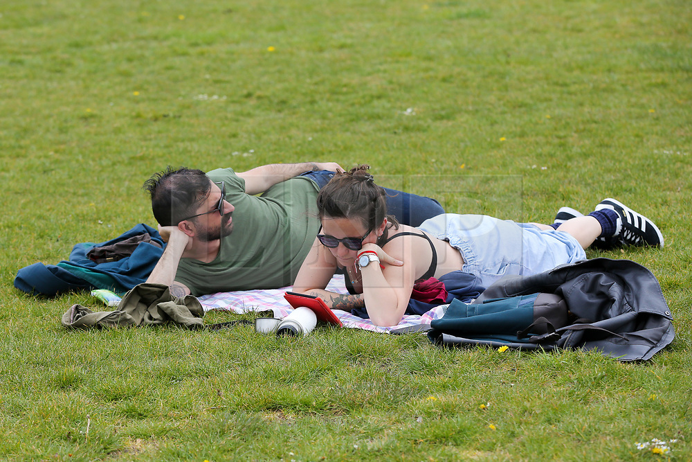 © Licensed to London News Pictures. 09/05/2021. London, UK. A couple enjoy the warm weather in Finsbury Park, north London. According to the Met Office, a temperature of 20 degrees celsius is expected on Sunday.  <br /> <br /> *** Permission Granted *** <br /> <br /> Photo credit: Dinendra Haria/LNP