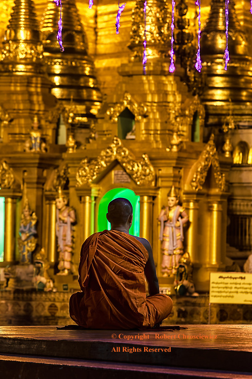 Buddhist Halo: A seated monk is captured in front of the green light that forms a Halo around his head, Shwedagon Pagoda, Yangon Myanmar.