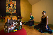 Buddhists meditate in silence for 30 minutes in their Shrine Room at the Rivendell Buddhist Retreat Centre, England. A middle-aged man and a younger woman sit in a meditative cross-legged position in order to relax their bodies and free their minds for this period of inner-contemplation. In front of the couple is a model of their retreat centre, a house now run by the Triratna Buddhist Community. Once a Victorian country rectory for the local vicar in this East Sussex village, it now houses facilities for the spiritual and the peaceful, having escaped for a brief time, the pressures of modern life. Beyond are two Buddhas on a tapestry and as a statue. The community web address is www.rivendellretreatcentre.com.