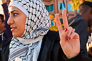 """31 JANUARY 2011 - TEMPE, AZ: A woman flashes a """"peace"""" during a demonstration in Tempe, AZ, supporting democracy in Egypt About 200 people marched through central Tempe, AZ, near the Arizona State University campus Monday afternoon. The rally was organized by the Arab American Association of Arizona in solidarity with the ongoing pro-democracy rallies and demonstrations in Egypt and other Arab countries.    Photo by Jack Kurtz"""