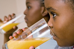 Boy and girl drinking glasses of orange juice,