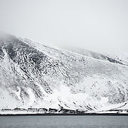 Mountains rising up from the shoreline at Whalers Bay on Deception Island. Deception Island, in the South Shetland Islands, is a caldera of a volcano and is comprised of volcanic rock.