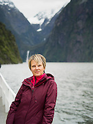 Tourist poses on a scenic cruise on Milford Sound, Fiordland National Park, New Zealand; Mount Pembroke and Stirling Falls in the background
