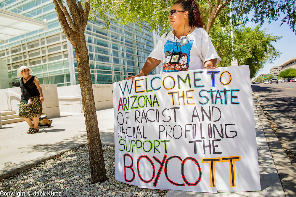01 AUGUST 2012 - PHOENIX, AZ:      JOSEPHINE NEVAREZ, stands in a solitary picket in front of the US Courthouse in Phoenix Wednesday. About 200 people, mostly Latino immigrants' rights and civil rights activists, gathered in front of the Sandra Day O'Connor Courthouse in Phoenix Wednesday to pray on what is expected to be the last day of testimony in the racial profiling trial against Maricopa County Sheriff Joe Arpaio. The suit, brought by the ACLU and MALDEF in federal court against Maricopa County Sheriff Joe Arpaio, alleges a wide spread pattern of racial profiling during Arpaio's ''crime suppression sweeps'' that targeted undocumented immigrants. U.S. District Judge Murray Snow granted the case class action status opening it up to all Latinos stopped by Maricopa County Sheriff's Office deputies during the crime sweeps. The case is being heard in Judge Snow's court.PHOTO BY JACK KURTZ