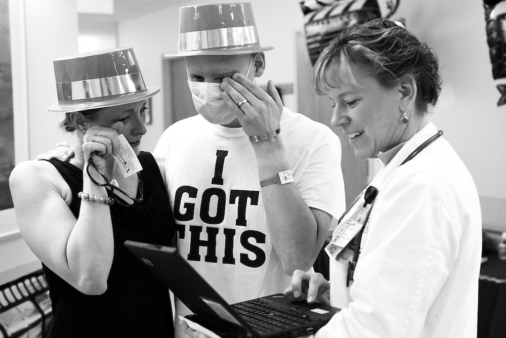 Chris Brown and his wife Alicia receive news that his recent bone marrow biopsy is free of leukemia from Dr. Elizabeth Bengston after a month in treatment and recovery in the inpatient oncology unit at DHMC in Lebanon, N.H. Saturday, July 11, 2015. The Browns wore plastic top hats while aiming to walk one mile in the unit's Hollywood themed indoor Prouty. Chris Brown, who is being treated for acute myeloid leukemia, plans to ride in next year's Prouty fundraiser following a stem cell transplant.  (Valley News - James M. Patterson)<br /> Copyright © Valley News. May not be reprinted or used online without permission. Send requests to permission@vnews.com.