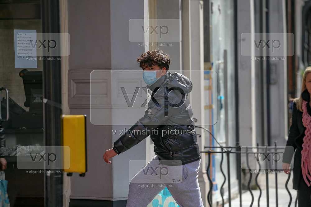 A man wearing a face protective mask in central London is seen walking into a pub on Saturday, March 21, 2020. For most people, the new coronavirus causes only mild or moderate symptoms, such as fever and cough. For some, especially older adults and people with existing health problems, it can cause more severe illness, including pneumonia. (Photo/Vudi Xhymshiti)