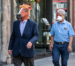 © Licensed to London News Pictures. 23/07/2020. London, UK. A man walks down the Kings Road in Chelsea while wearing a horses head mask. Face masks will be compulsory in shops, takeaway cafes and supermarkets from 24th July and enforced by the Police, with anyone who fails to wear one liable to a £100 fine. Photo credit: Alex Lentati/LNP