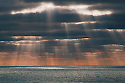 Sunlight through clouds, dark skies, cloud layers, sun rays on the Pacific Ocean, ocean shores, Cardiff-by-the-Sea, San Diego County, California parks