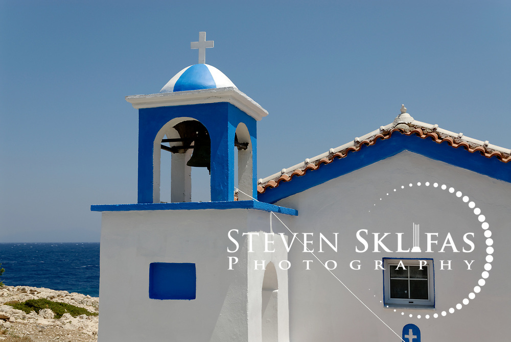 Samos. Greece. Blue and white washed Greek Orthodox Church with a bell tower at the northern seaside town of Avlakia. In the background are the blue waters of the Aegean Sea.