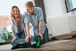 Couple packing suitcase