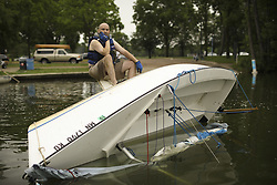 June 11, 2017 - Minneapolis, MN, U.S.A - Martin Conroy waited for some help from others as he attempted to right his overturned sailboat on Lake Nokomis Sunday afternoon. When he drove past the lake after the storm Sunday morning, ''I saw that I was the only one flipped, so I went home and changed for my unplanned afternoon adventure.''    ]  JEFF WHEELER • jeff.wheeler@startribune.com ....High winds and rain hit the metro area hard Sunday morning, June 11, 2017, downing trees and knocking out power in some areas. (Credit Image: © Jeff Wheeler/Minneapolis Star Tribune via ZUMA Wire)