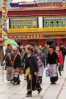 Tibetan pilgrims circumambulate through Barkhor Square and along The Barkhor (the route around the most sacred temple in Tibet, Jokhang Temple). Lhasa, Tibet, China.