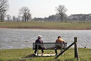 Nederland, Batenburg, 5-4-2020 Twee vrouwen, moeder en dochter,zitten op een bankje aan de oever van de Maas tijdens de coronacrisis . Mensen moeten ook met het mooie weer zoveel mogelijk thuis of binnen blijven . Het is lekker voorjaarsweer . Er zijn niet veel mensen in dit natuurgebied, de Liendense waard . De uiterwaarden van de Maas bij het stadje zijn heringericht. Er is onder meer een nevengeul aangelegd waardoor er geregeld water door het gebied stroomt. De uiterwaarden ontwikkelen zich hierdoor tot een interessant natuurgebied. Het is een project ihkv ruimte voor de rivier ., de meanderende maas om in tijden van hoogwater een betere afvoer te hebben. Foto: Flip Franssen