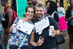 "London, August 29th 2016. A couple display their signs urging the tens of thousands of revellers to ""enjoy Carnival"" during day two of Europe's biggest street party, the Notting Hill Carnival."
